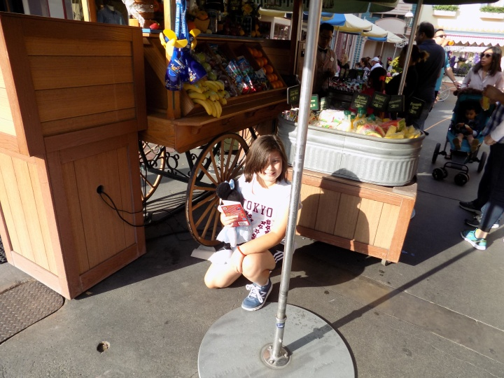 Pointing out a less obvious Mickey in the undercarriage of the fruit cart