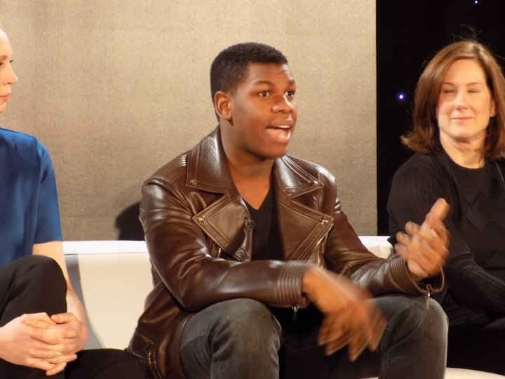 John Boyega at the Star Wars: The Force Awakens press event answering questions from Mindy Kaling and the press