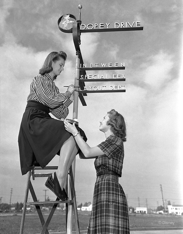 This 1940 publicity photo shows employee Eva Sinclair touching up the lettering to the iconic sign at The Walt Disney Studios intersection of Mickey Avenue and Dopey Drive while Jackie Walker holds the paint ready for her. The sign was originally created as a movie prop for the film The Reluctant Dragon (1941).