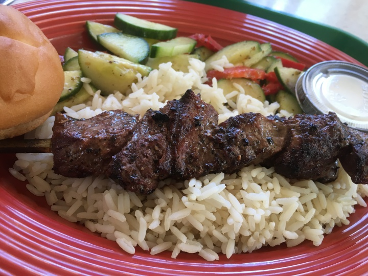 My gluten-free steak skewer platter with rice, Tzatziki sauce, cucumber salad, and gluten-free roll