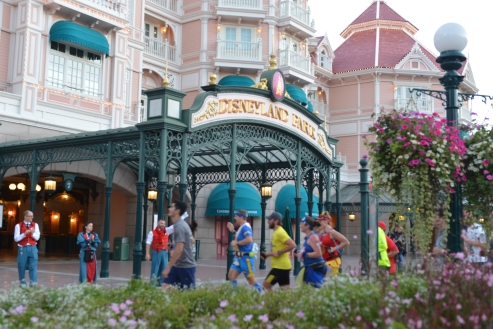 Athletes running through the entrance to Disneyland Park in Paris. © Disney / As to Disney properties